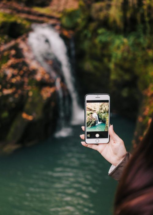 Woman taking photo of a waterfall with her smartphone