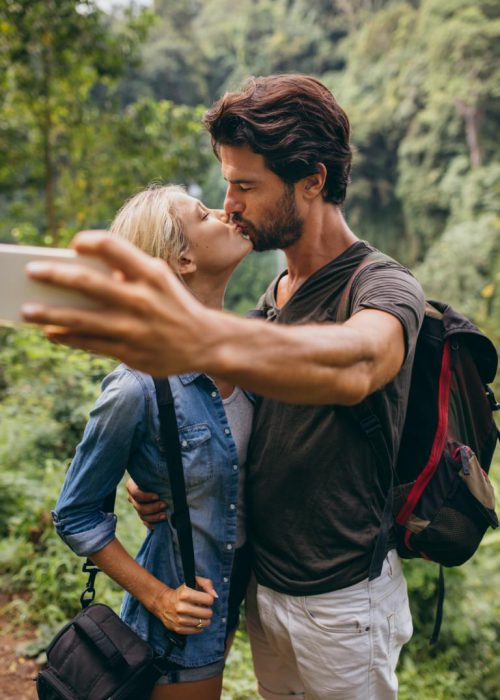 Loving young couple kissing and taking self portrait with their cell phone. Couple in love taking self picture in forest.